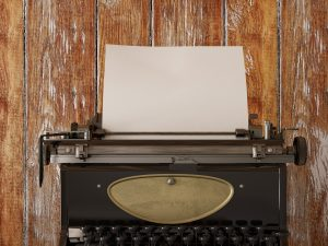 Typewriter sitting on wooden floor, ready for use